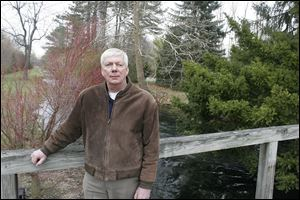 Doug Entenman of Fostoria bought part of Castalia Farms with a $620,000 bid. He's on a wooden bridge over Cold Creek, a pristine waterway filled with trout.