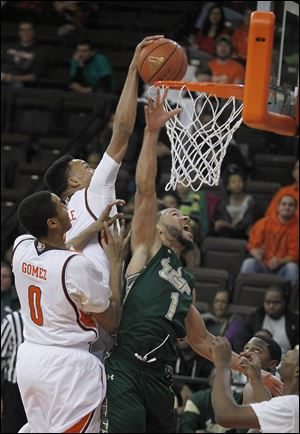Bowling Green State University's JD Tisdale goes in for a slam dunk over South Florida's Musa Abdul-Aleem, while teammate Josh Gomez looks on. Tisdale finished with two points in the loss to the Bulls.