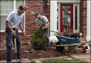 Paul Ewersmann, left, and Jeff Emege, plant a new dwarf alberta spruce in front of the Schneider home in St. Charles, Mo. The family is spending about $5,000 to repair damage done by a tornado.