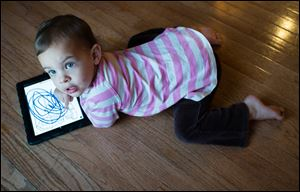 Reagan Zaal, 2, colors with an iPad at her home in Middletown, Md. More parents are looking for tablets for their children who have become accustomed to smart phones, iPads, and Kindles.