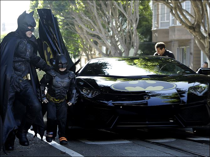Boys Batman Wish BATMOBILE Miles Scott, dressed as Batkid, second from left, exits the Batmobile with Batman to save a damsel in distress in San Francisco today.