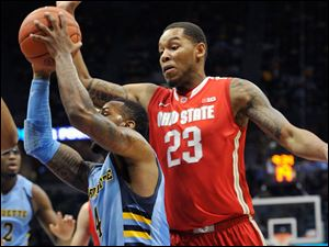 Marquette's 's Todd Mayo, left, drives to the basket as Ohio State's' Amir Williams (23) defends during the first half.