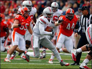 Ohio State quarterback Braxton Miller, center, is chased by Illinois defensive lineman Austin Teitsma (44) and defensive lineman Houston Bates (55) during the first half.