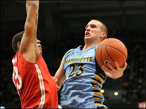 Ohio State's' Amir Williams, left, defends as Marquette's 's Jake Thomas (23) drives to the basket during the first half.