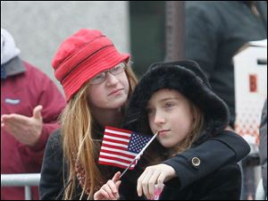 Kelsey Colter, 12, left, and her sister Aubrey Colter, 10, of Riga, Michigan watching the parade.