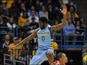 Marquette's Jamil Wilson (0) flies through the air trying to block the shot of Ohio State's' Lenzelle Smith Jr.