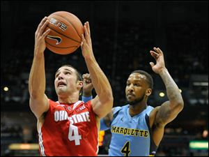 Ohio State's' Aaron Craft (4) drives to the basket past Marquette's 's Todd Mayo (4) during the second half.
