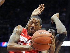 Ohio State's' Lenzelle Smith Jr., left, drives to the basket against Marquette during the second half.