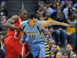 Ohio State's' Shannon Scott left, and Marquette's Juan Anderson (10) fight for the ball during the first half.