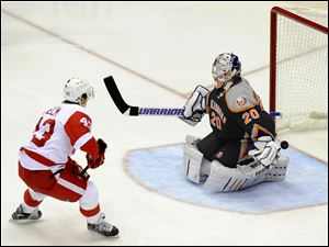 Detroit Red Wings center Darren Helm (43) shoots the puck past New York Islanders goalie Evgeni Nabokov (20) to score in the first period of an NHL hockey game on Saturday, in Uniondale, N.Y. Nabokov left the ice with an injury after the play.