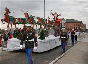 Santa Claus rrives with his sleigh of reindeer, escorted by members of the U.S. Marine Corps, as The Blade's 26th Annual Holiday Parade, sponsored by The Taylor Automotive Family, makes its way down Summit Street.