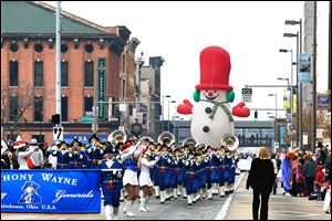 Members of tjhe Anthony Wayne High School band are followed by a huge balloon of Frosty the Snowman. The parade, a downtown Toledo tradition, offered several floats for spectators to enjoy.