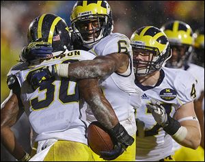 Michigan's Thomas Gordon, left, celebrates with Raymon Taylor after Gordon intercepted a pass in the third overtime.