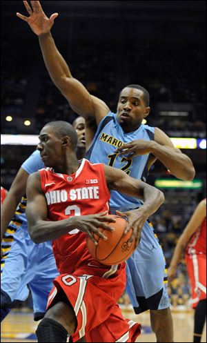 Ohio State's' Shannon Scott drives around Marquette's 's Derrick Wilson during the second half of an NCAA college basketball game Saturday, Nov. 16, 2013, in Milwaukee. Ohio State defeated Marquette 52-35. (AP Photo/Jim Prisching)