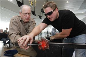 Toledoan and former Air Force B52 pilot Rick Hartley, left, makes a glass flower with the help of glass facilitator Brandon Price during glassblowing day for veterans at the Toledo Museum of Art Glass Pavilion.