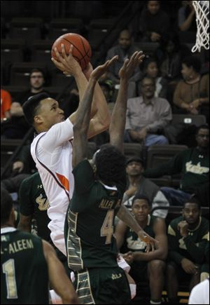 BGSU's JD Tisdale goes over South Florida's Corey Allen Jr. for two points during basketball game at the BGSU Stroh Center in Bowling Green.