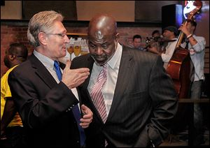 Campaign consultant Mark Luetke, left, confers with Mayor Bell during an election night party. Mr. Luetke says the mayor's message resonated with voters, but some couldn't get past his support of Senate Bill 5.