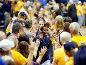 The Rockets' Janelle Reed-Lewis leads the Rockets out through a tunnel of fans.