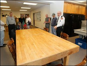 Sylvania Township Fire Department deputy chief Michael Ramm, right, explains to visitors that the table was made from a section of the hardwood floor of the previous station no. 1 by firefighter Jeremy Gillen.  A