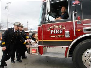 Maintaining a firefighter tradition, a truck is pushed into Fire Station 1 in Sylvania to mark its opening. From left: Sylvania Township Deputy Chief Mike Froelich, Chief Jeff Kowalski, Deputy Chief Mike Ramm, and firefighter Todd Walters. Driving is firefighter Mike Sobb.