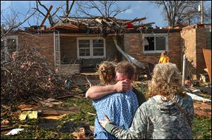 Ray Baughman embraces relatives shortly after a tornado destroyed his home in Pekin, Ill., a city on the Illinois River and south of Peoria. The city sustained significant damage, according to media reports.