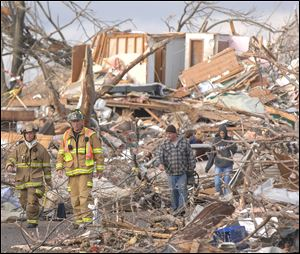 Firefighters survey the destruction on a street in Washington, Ill., after a tornado unleashed its fury Sunday. Homes and buildings were destroyed in seconds by the swift-moving storm.