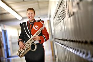 Bedford High School senior Sarah Balazs shows off the band uniform the boosters group wants to purchase.
