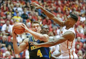 Michigan forward Mitch McGary, left, looks to pass around Iowa State forward Melvin Ejim during the second half in Ames, Iowa.