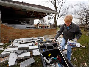 Sherri Warkentien cleans up debris from the home of her boyfriend, Ron Armsrtrong, on South Lallendorf Road in Oregon.
