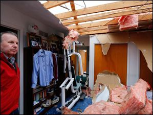 Robert Zeller looks at damage done to a bedroom at his home on South Lallendorf Road in Oregon, Monday. Mr. Zeller and his wife were at home when Sunday's storm blew through.