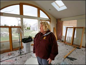 Tammy Kreais looks around her storm damaged home.