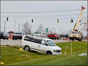 A van sits in the ditch near the corner of State Rt. 795 and Oregon Road in Perrysburg Township Monday.