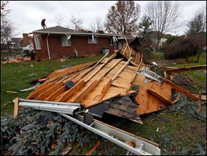 The roof of Robert Zeller's home on outh Lallendorf Road, lies in his neighbor's yard, Monday.