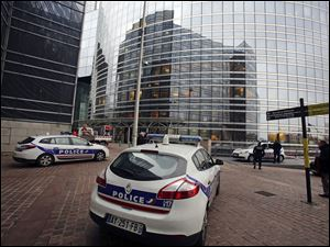 Police cars park near the entrance of the Societe General Bank headquarters in La Defense business district, west of Paris, today. Soon after a shooting at newspaper Liberation, shots were fired at the headquarters of the French bank.