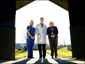 Dr. Christopher Cooper, center, with Holly Burtch, left, and Pamela Brew