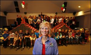 Cheryl Beal, coordinator of Operation Christmas, stands in front of 1,000 shoe boxes and some of the others who made it happen, at Bedford First Church of the Nazarene in the Lambertville area.