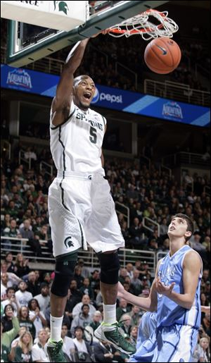 Michigan State's Adreian Payne dunks over Columbia's Luke Petrasek on Friday in East Lansing, Mich.