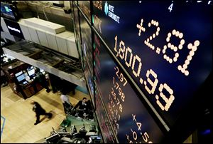A board above New York Stock Exchange's trading floor shows the Standard & Poor's 500 index crossing the 1,800 threshold Monday.