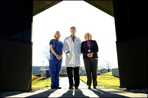 Dr. Christopher Cooper, center, with Holly Burtch, left, and Pamela Brewster stand on the University of Toledo Health Science Campus, the former Medical College of Ohio. His team's findings were revealed in Dallas at a national meeting of scientists sponsored by the American Heart Association.