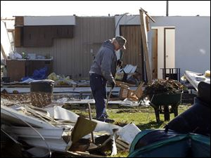 Dave Smith, left, with city utilities maintenance, cleans up debris in a yard in front of a house that was leveled by the tornado on Jerry City Road at the Huffman Road intersection.