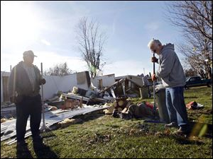 Jerry City Mayor Gene Cox, right, rakes the debris in a yard in front of a house that was leveled by the tornado. Dave Smith, left, with city utilities maintenance helps the mayor with the clean-up.
