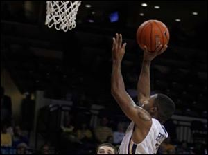 Toledo's Julius Brown drives to the basket as a teammate and Florida A&M player watch.