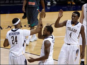 Toledo's  J.D. Weatherspoon, Rian Pearson, and Justin Drummond high-five during basketball game against Florida A&M.