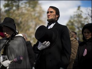 John Voehl portraying President Abraham Lincoln,  covers his heart during a ceremony commemorating the 150th anniversary of the dedication of the Soldiers' National Cemetery and President Abraham Lincoln's Gettysburg Address, Tuesday.