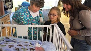 Allison Herr, 10, of Metamora, looks at a baby in the neonatal intensive care unit at Mercy St. Vincent Medical Center with nurse Cheryl Thacker, left, and her mother, Jenny Herr.