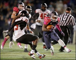 Rockets running back Kareem Hunt tries to get past Jimmie Ward of Northern Illinois. Hunt finished with 91 yards on 19 carries.