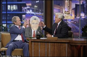 Geroge Bush on Jay Leno showing the late-night host his portrait.