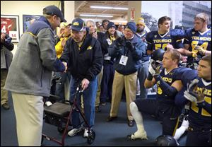 Former Toledo Rockets football coach Frank Lauterbur is applauded in the Rockets' locker room prior to the Rockets' spring game at the Glass Bowl on Friday, April 12, 2013.