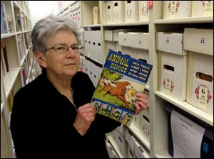 Maggie Thompson poses with 'Animal Comics' in the addition to her Wisconsin home that houses her tens of thousands of comic books. Thompson has put about 500 of her most treasured issues up for auction, including copies of  'Journey Into Mystery' No. 83 and the first issue of 'The Avengers.'