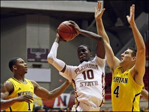 Florida State forward Okaro White, center, goes to the basket against Mi